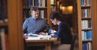 Adult skills: Two mature students study in a library