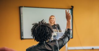 Woman raises her hand to suggest an idea
