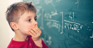 Cognition: Little boy looks confused at equation on a blackboard