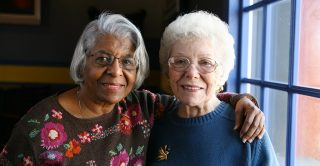 Two older ladies pose for a photo together