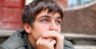 Sad teenage boy sits alone