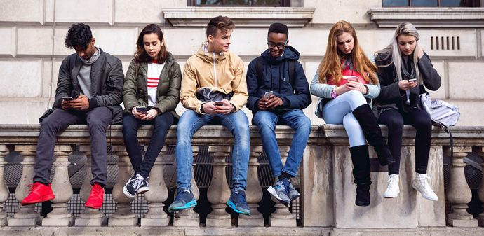 Teenagers sit on a wall and check their social media