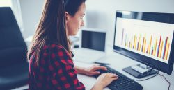 Woman looks at bar charts on her computer