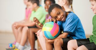 Child sits with a football in PE class