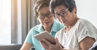 Twins using a tablet together