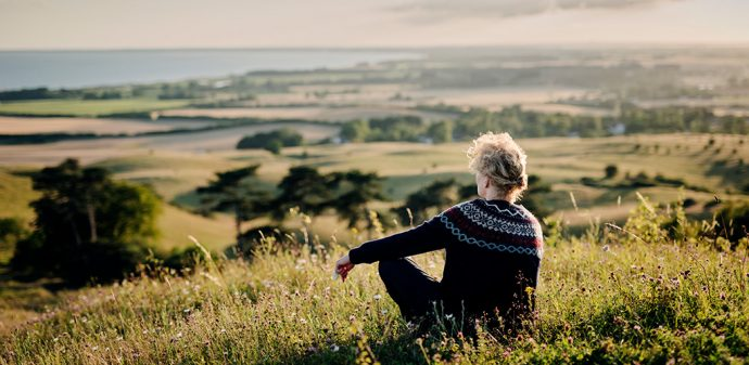 Woman sitting on a hill looking out over a view of fields and woods