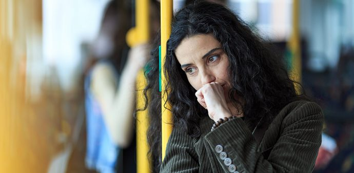 sad looking middle aged woman leans against a pole on public transport