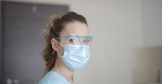Woman wearing face shield and medical mask