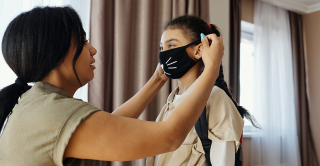 a mother helps her young daughter put on a face mask