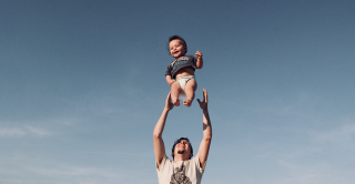 Toddler being thrown up in the air by his dad standing below ready to catch him