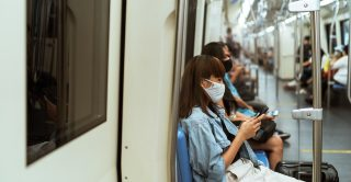 Woman wearing a mask sitting on a train