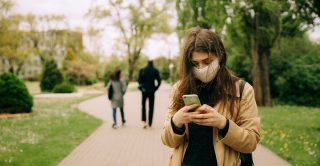 Woman wearing a mask in the park using her phone