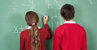 School children write on the blackboard