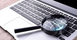 Magnifying glass placed on a laptop keyboard