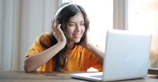 Young woman wearing headphone uses her laptop for video call