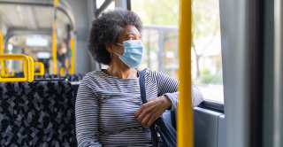 Woman wearing a face mask sits on a bus looking out the window